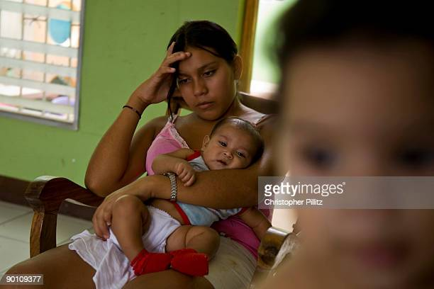 Marta holds her head in her hand as her young baby sits in her lap feeling forlorn and disenchanted with life Together with 11 other 'child mothers'...