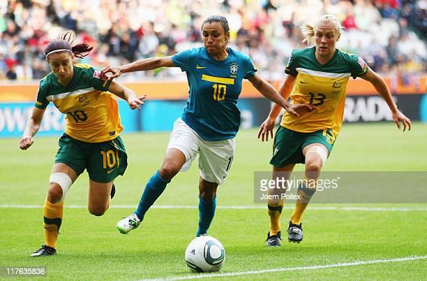 Marta of Brazil and Servet Uzunlar and Tameka Butt of Australia battle for the ball during the FIFA Women's World Cup 2011 Group D match between...