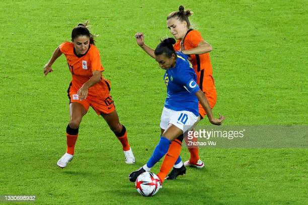 Marta of Brazil competes for the ball during the Women's First Round Group F match on day one of the Tokyo 2020 Olympic Games at Miyagi Stadium on...
