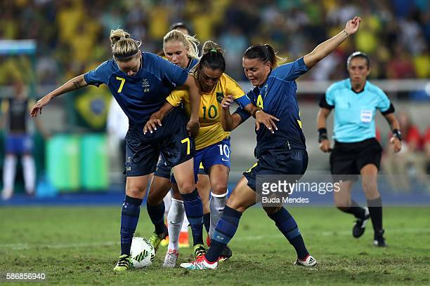 Marta of Brazil fights for the ball with Lisa Dahlkvist and Emilia Appelqvist of Sweden during the Women's Group E first round match between Brazil...