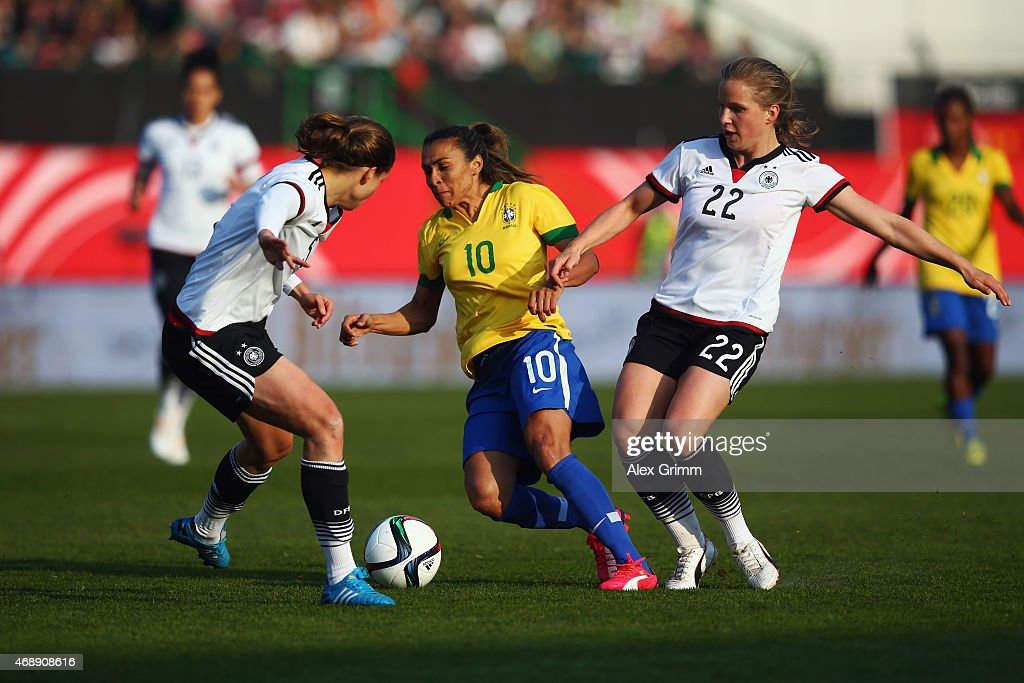 Marta (C) of Brazil is challenged by Annike Krahn (L) and Tabea Kemme of Germany during the Women's International Friendly match between Germany and Brazil at Trolli-Arena on April 8, 2015 in Fuerth, Germany.