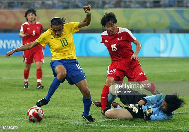 Marta of Brazil is closed down by Kyong Sun Sonu and goalkeeper Myong Hui Jon of North Korea during the Women's First Round Group F match between...