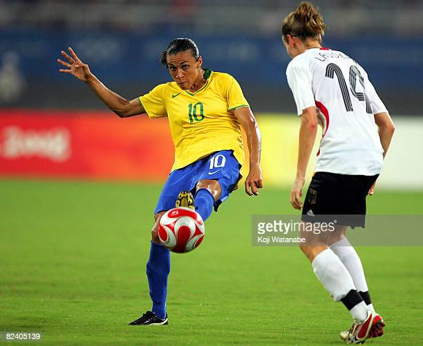 Marta of Brazil passes the ball past Simone Laudehr of Germany during the Women's Semi Final match between Brazil and Germany at Shanghai Stadium on...