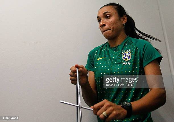 Marta of Brazil plays the triangle as she walks with her teammates to their dressing room prior to the FIFA Women's World Cup 2011 Group D match...