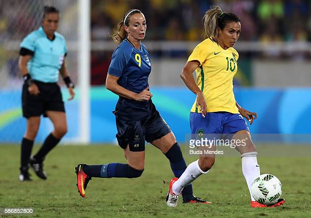Marta of Brazil runs with the ball past Kosovare Asllani of Sweden during the Women's Group E first round match between Brazil and Sweden on Day 1 of...