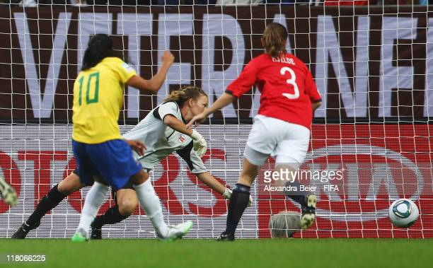 Marta of Brazil scores her first goal against Maren Mjelde and goalkeeper Ingrid Hjelmseth of Norway during the FIFA Women's World Cup 2011 group D...