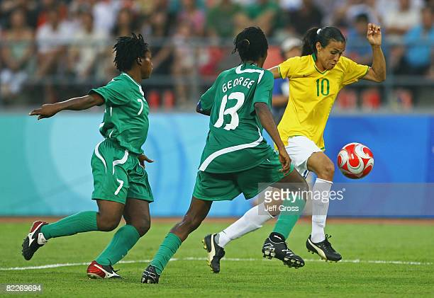 Marta of Brazil takes the ball past Stella Mbachu and Christie George of Nigeria during the Women's First Round Group F match between Nigeria and...