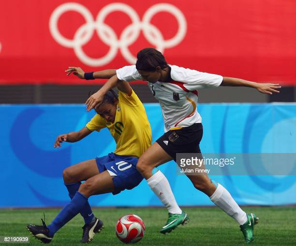Marta of Brazil tangles with Linda Bresonik of Germany during the women's preliminary group F match between Germany and Brazil at Shenyang Stadium on...