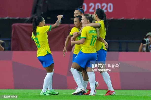 Marta of Team Brazil celebrates with teammates Debinha and Andressinha after scoring their side's third goal during the Women's First Round Group F...