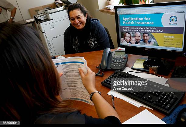 Marta Viera smiles as her application for Obamacare is completed as enrollment counselor Jessie Orozco signs up people for Obamacare at St. John's...