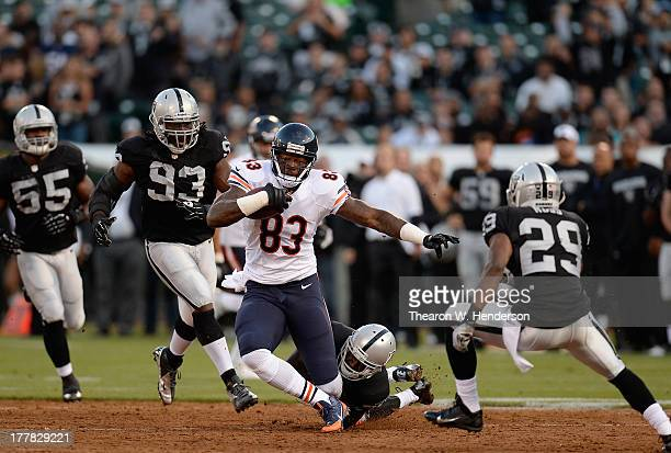 Martellus Bennett of the Chicago Bears after catching a short pass gets tackled by DJ Hayden of the Oakland Raiders in the first quarter at O.co...