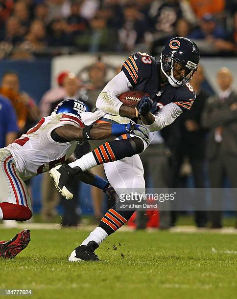 Martellus Bennett of the Chicago Bears is tackled by Spencer Paysinger of the New York Giants at Soldier Field on October 10 2013 in Chicago Illinois...