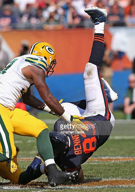 Martellus Bennett of the Chicago Bears is upended after making a catch and is hit by Jay Elliott of the Green Bay Packers at Soldier Field on...