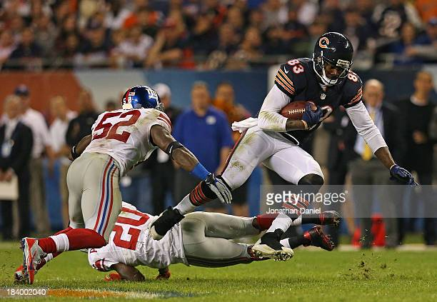 Martellus Bennett of the Chicago Bears moves between Spencer Paysinger and Prince Amukamara of the New York Giants at Soldier Field on October 10...