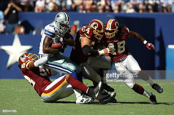 Martellus Bennett of the Dallas Cowboys is tackled by a host of Washington Redskins defenders at Texas Stadium on September 28 2008 in Irving Texas...