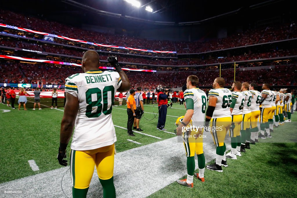 Martellus Bennett #80 of the Green Bay Packers raises his fist during the national anthem prior to the game between the Green Bay Packers and the Atlanta Falcons at Mercedes-Benz Stadium on September 17, 2017 in Atlanta, Georgia.