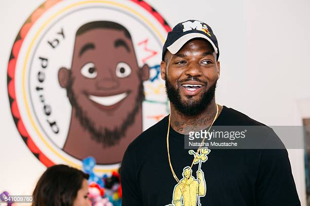 Martellus Bennett stands in front of his animated portrait during the Hey AJ Imagination Lounge Pop Up on June 17 2016 in Boston Massachusetts
