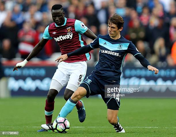 Marten de Roon of Middlesbrough is put under pressure from Cheikhou Kouyate of West Ham United during the Premier League match between West Ham...