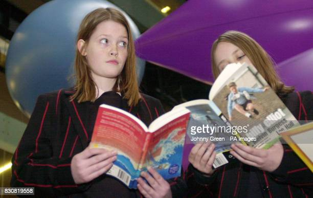 Martha Cooke and Poppy McPherson both from Lady Margarets School in Fulham west London read books as Performance Artists behind them create a...