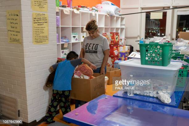 Martha Elizabeth Hernandez who came from California to volunteer lets a boy choose a toy at Centro San Juan Diego shelter on November 4 2018 in El...