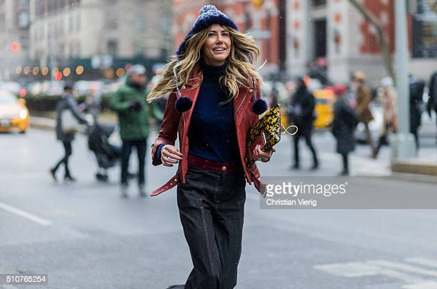 Martha Graeff wearing a red leather jacket and wide dark denim jeans seen outside Tommy Hilfiger during New York Fashion Week Women's Fall/Winter...