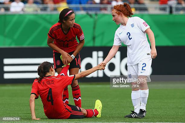 Martha Harris of England shakes hands with Paulina Solis and Greta Espinoza of Mexico after the FIFA U20 Women's World Cup Canada 2014 group C match...