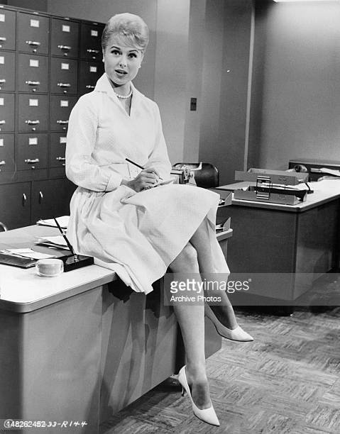 Martha Hyer taking notes while sitting on top of desk in a scene from the film 'The Man From The Diners' Club' 1963