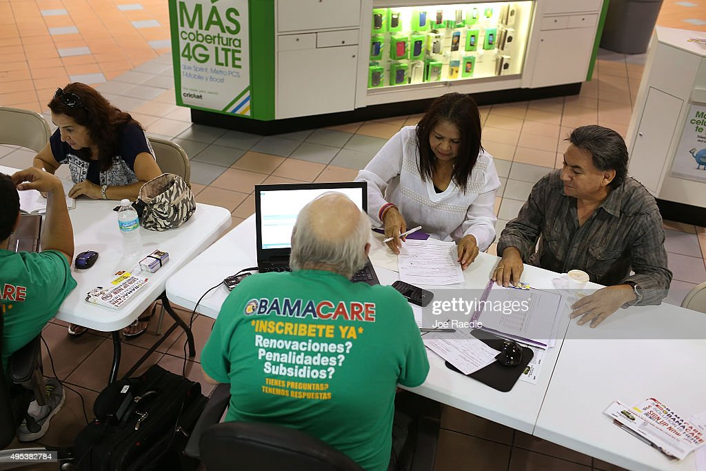 Martha Lucia, Bienvendida Barreno and Jorge Baquero (L-R) sit with insurance agents from Sunshine Life and Health Advisors as they discuss plans available in the third year of the Affordable Care Act at a store setup in the Mall of the Americas on November 2, 2015 in Miami, Florida. Open Enrollment began yesterday for people to sign up for a 2016 insurance plan through the Affordable Care Act.