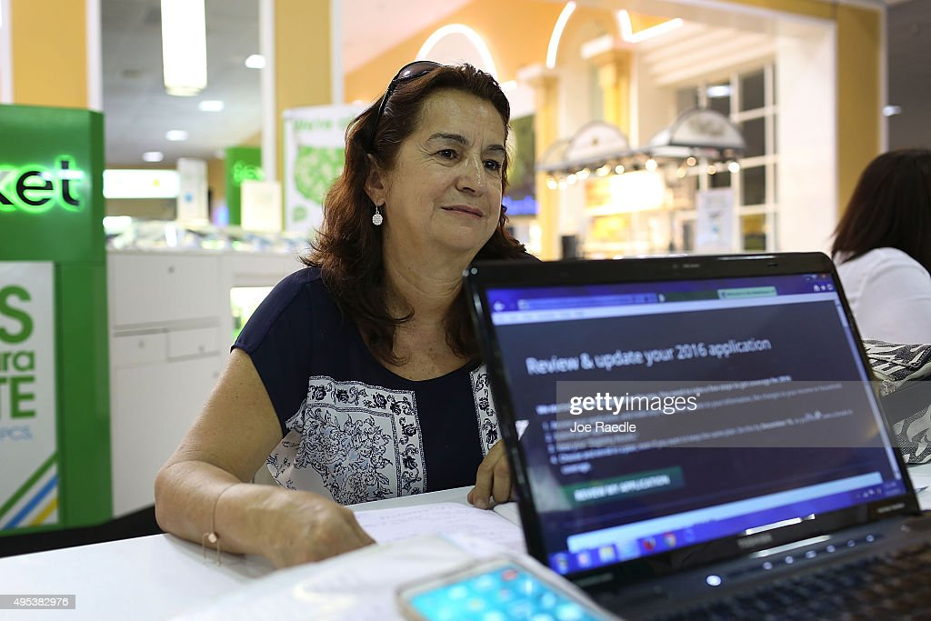 Martha Lucia sits with an insurance agent from Sunshine Life and Health Advisors as she picks an insurance plan available in the third year of the Affordable Care Act at a store setup in the Mall of the Americas on November 2, 2015 in Miami, Florida. Open Enrollment began yesterday for people to sign up for a 2016 insurance plan through the Affordable Care Act.
