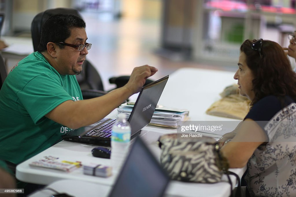 Martha Lucia (R) sits with Rudy Figueroa, an insurance agent from Sunshine Life and Health Advisors, as she picks an insurance plan available in the third year of the Affordable Care Act at a store setup in the Mall of the Americas on November 2, 2015 in Miami, Florida. Open Enrollment began yesterday for people to sign up for a 2016 insurance plan through the Affordable Care Act.