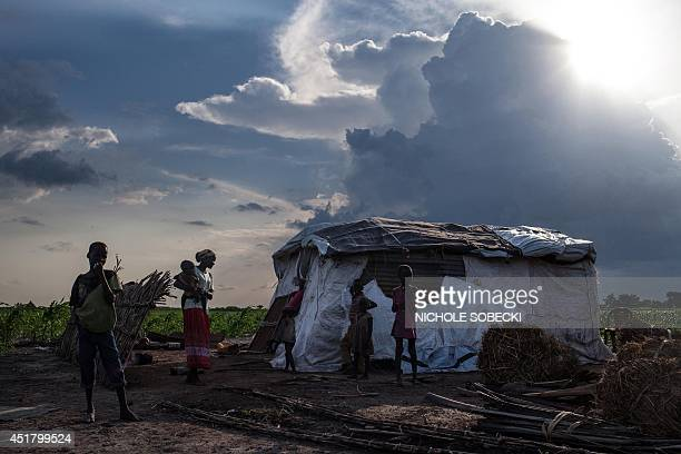 Martha Nyarueni and her family stand outside their home outside the town of Leer South Sudan after receiving aid package on July 5 2014 In January...