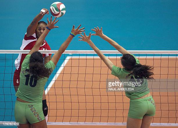 Martha Revuelta and teammate Gema Leon of Mexico try the stop the ball of Jessenia Euseda of Peru in the Women's Volleyball Pool B Preliminary Round...