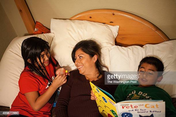 Martha Rios center reads with her son Christian Pereida right and her daughter Yehaira Pereida left from the book Pete the Cat after dinner in...