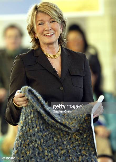 Martha Stewart smiles as she holds up the much publicized poncho she wore when she left prison during a speech to an audience of her employees and...