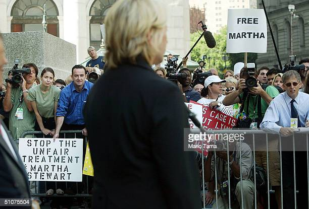 Martha Stewart supporters look on as she speaks to the media outside Federal Court after her sentencing hearing July 16 2004 in New York City Stewart...
