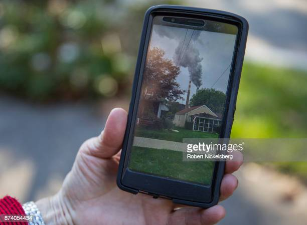 Marti Blake shows a picture she took nearby her home of the smoke stack of the 47year old Cheswick coalfired power plant October 27 2017 in...