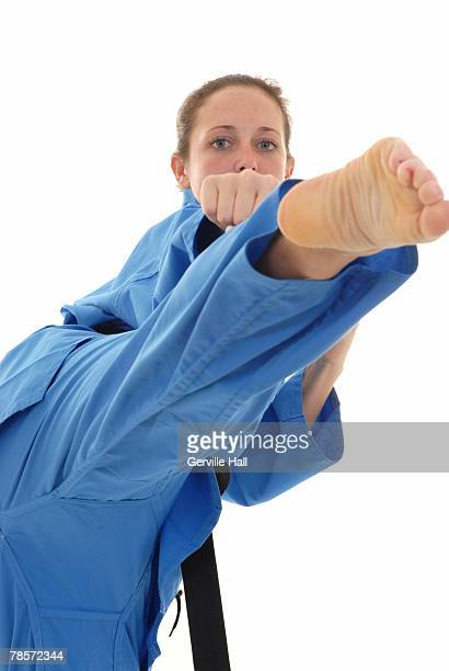 Martial artist executing a roundhouse kick.