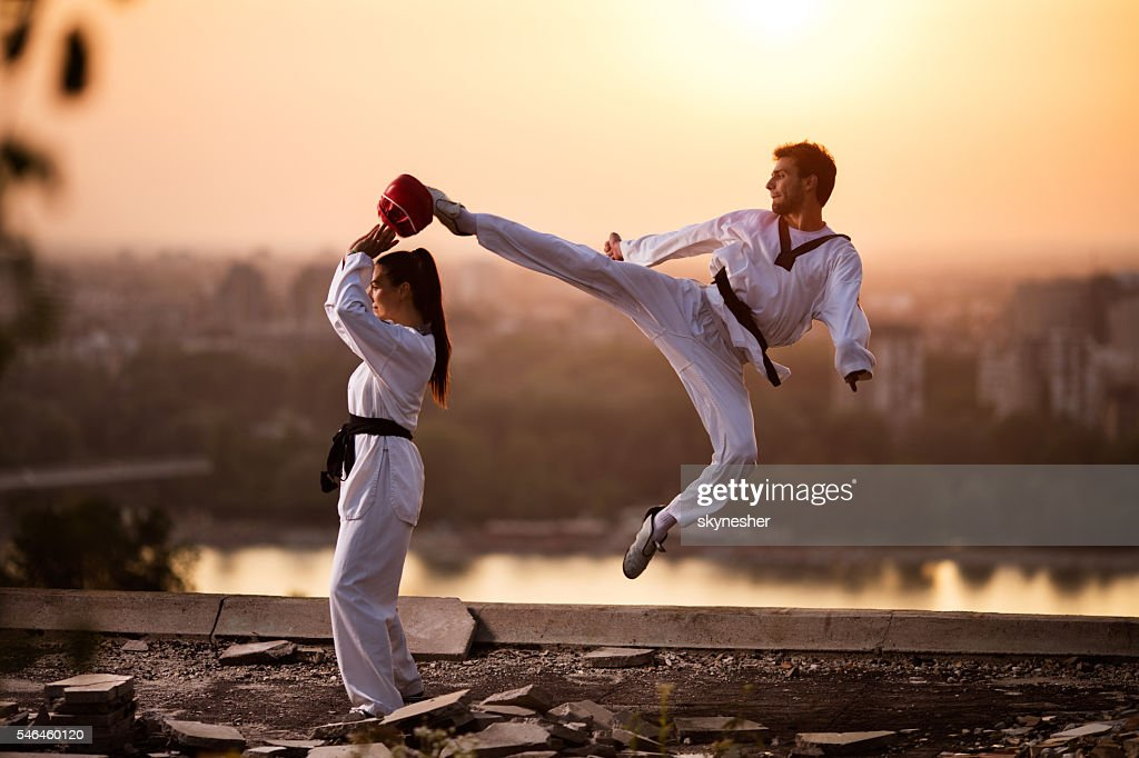 Martial artist fighter exercising with female partner at sunset. : Stock Photo