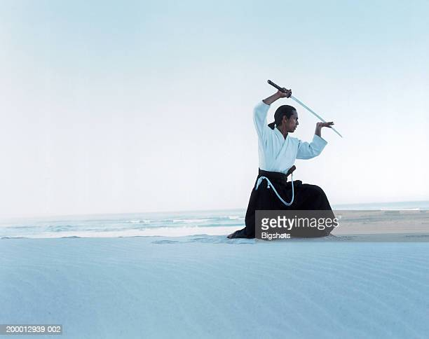 Martial artist kneeling with sword on beach
