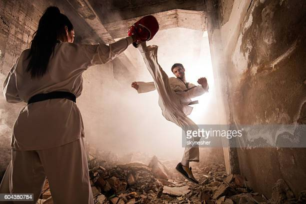 Martial artist practicing jump kick with female partner among ruins.