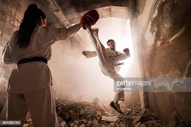 martial artist practicing jump kick with female partner among ruins. - taekwondo photos et images de collection