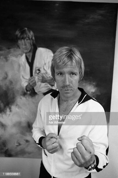 Martial arts action movie star Chuck Norris poses infant of action poster on the wall of his home in Palos Verdes Southern bcaliforia circa 1978