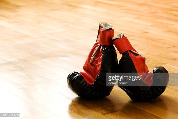 Martial arts boxing gloves lying on wooden floor