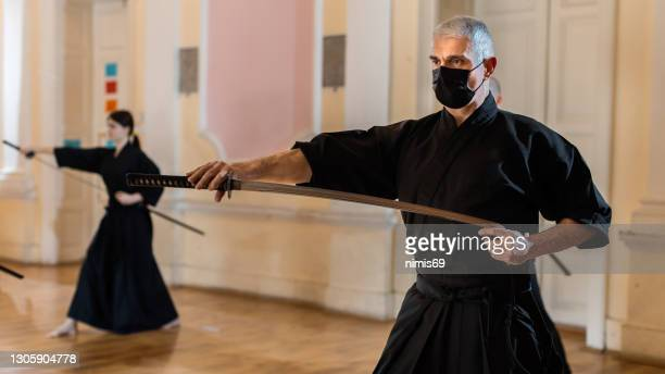 martial arts - iaido sensei met zwaard - vechtsport stockfoto's en -beelden