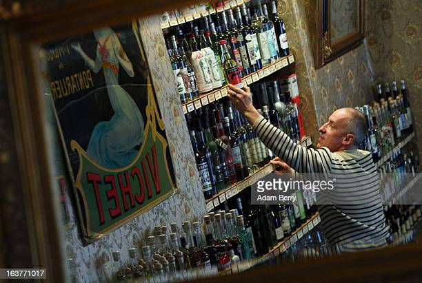 Martial Philippi owner of the Absinth Depot shop removes bottles of absinthe from a shelf on March 15 2013 in Berlin Germany The highly alcoholic...