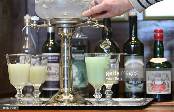 Martial Philippi owner of the Absinth Depot shop uses an absinthe fountain to pour water into glasses of absinthe on March 15 2013 in Berlin Germany...