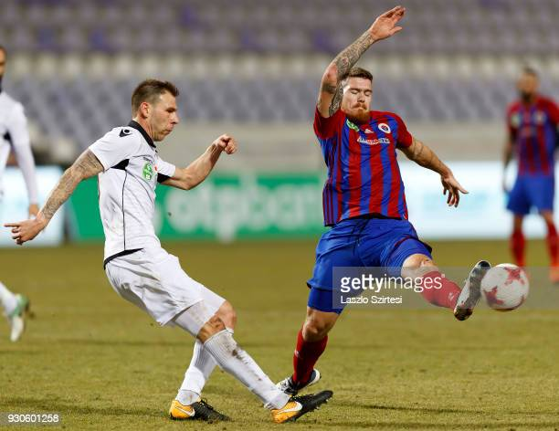 Martin Adam of Vasas FC tries to block the pass from Ivan Lovric of Budapest Honved during the Hungarian OTP Bank Liga match between Vasas FC and...