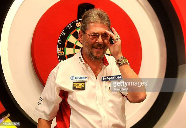 Martin Adams of England smiles after winning against David Cameron of Canada on day one of the BDO Lakeside World Professional Darts Championships at...