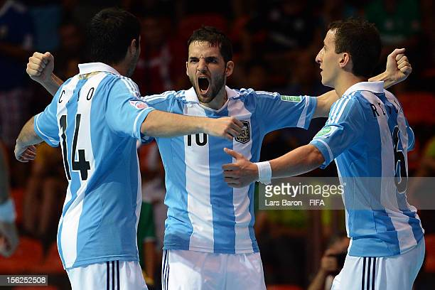 Martin Amas of Argentina celebrates with team mates Alan Calo and Maximiliano Rescia after winning the FIFA Futsal World Cup Round of 16 match...