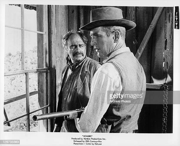 Martin Balsam looking at rifle holding Paul Newman in a scene from the film 'Hombre' 1967